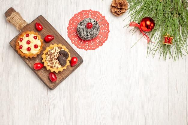 Vista de cima tortas de cacau e bagas e cornels na tábua de cortar bolo de cacau e folhas de pinheiro com brinquedos de natal no chão de madeira branco