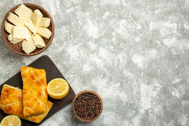 Vista de cima tortas de queijo tigelas de madeira com queijo e pimenta preta, tortas apetitosas e limão na tábua de corte no lado esquerdo da mesa