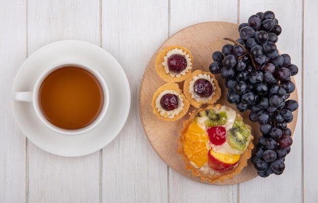 Vista de cima tortinhas com uvas pretas em um suporte com uma xícara de chá em um fundo branco