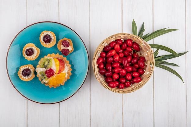 Vista de cima tortinhas de frutas em um prato azul com dogwood em uma cesta em um fundo branco