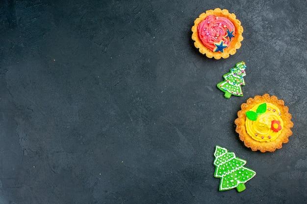 Vista de cima tortinhas pequenas biscoitos de árvore de natal em mesa escura, lugar livre