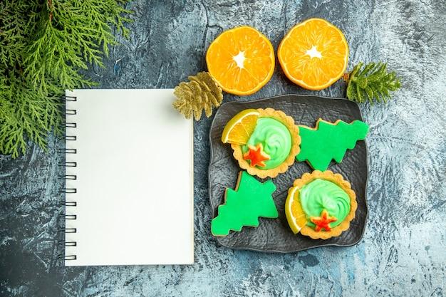 Vista de cima tortinhas pequenas, biscoitos de árvore de natal em placa preta, caderno de laranja cortado em mesa cinza