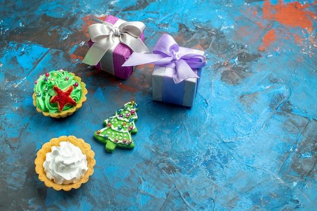 Vista de cima tortinhas pequenas presentes biscoitos de árvore de natal na mesa vermelha azul cópia local