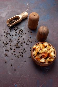 Vista de cima tostas secas com pimenta na mesa escura