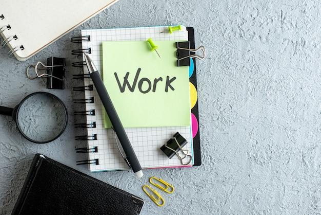 Vista de cima trabalho escrito nota no adesivo verde com bloco de notas e caneta no fundo branco cor trabalho escritório caderno faculdade escola de negócios
