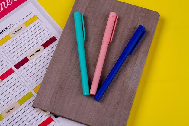 Vista de cima três canetas de feltro coloridas no livro.