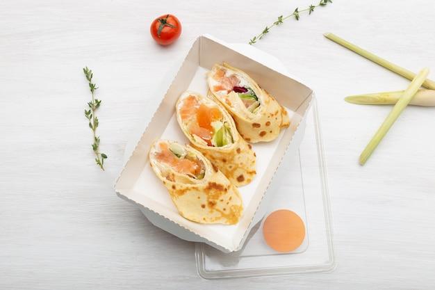 Vista de cima três fatias de panquecas com peixe vermelho, verduras e queijo em uma lancheira em uma mesa branca ao lado de verduras e legumes. conceito de nutrição adequada.