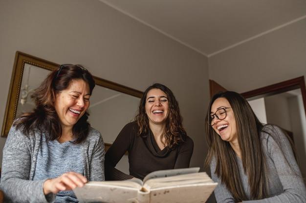 Vista de cima três mulheres, mãe e filhas, olhando um livro de memórias e rindo. união, conceito de família.