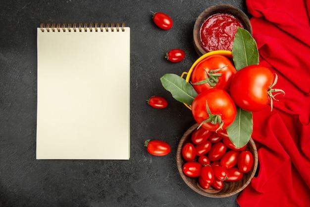Vista de cima um balde com tomates e folhas de louro tigelas com tomate cereja e toalha vermelha de ketchup um caderno em solo escuro