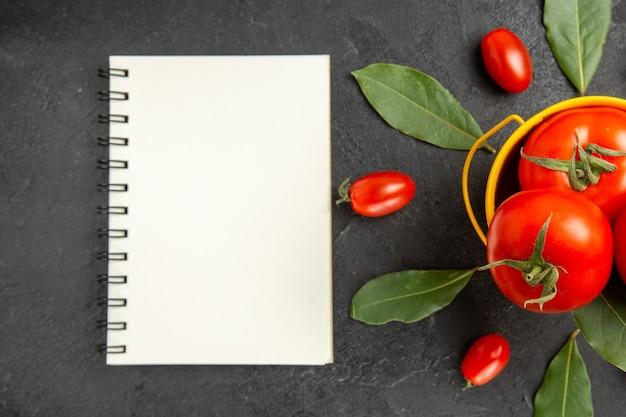 Vista de cima um balde com tomates em volta de tomates cereja e folhas de louro e um caderno em solo escuro