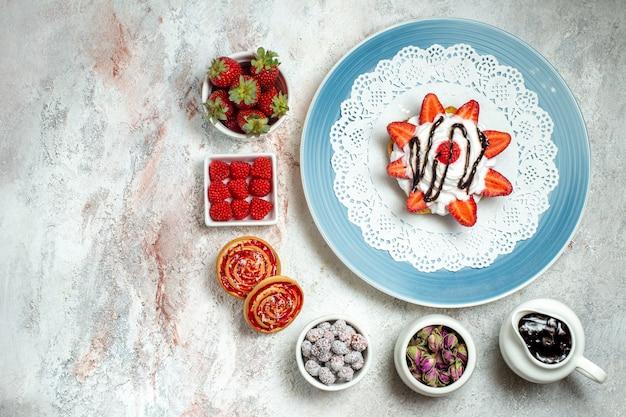 Vista de cima um bolo gostoso com biscoitos e frutas em branco