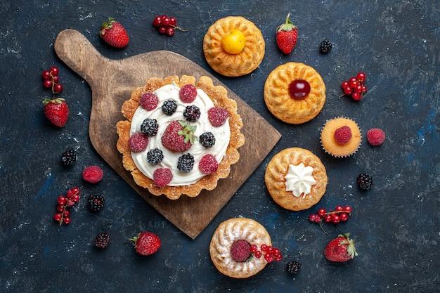 Vista de cima um bolo gostoso com creme e frutas vermelhas e biscoitos de pulseira na mesa escura.