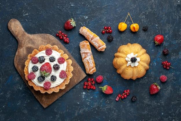Vista de cima um bolo gostoso com creme e frutas vermelhas junto com pulseiras na mesa escura.