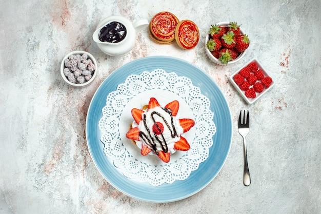 Vista de cima um bolo gostoso com creme e morangos frescos em branco