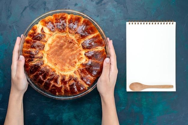 Vista de cima, um delicioso bolo assado redondo formado doce dentro da panela de vidro na mesa azul claro.