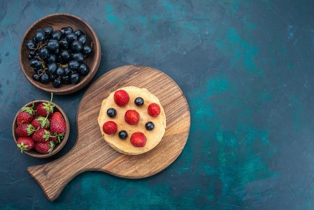 Vista de cima um pequeno bolo assado redondo formado com morangos frescos na superfície azul escura