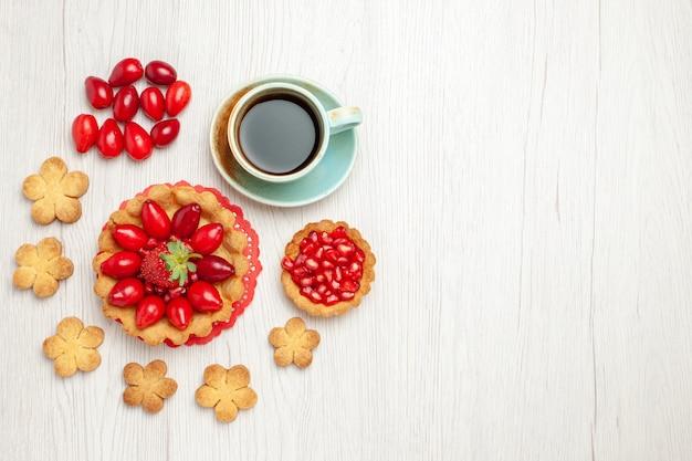Vista de cima um pequeno bolo com biscoitos de frutas e uma xícara de chá na mesa branca