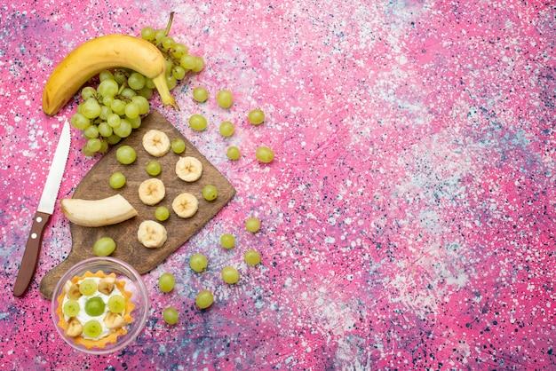 Vista de cima um pequeno bolo com uvas frescas e bananas na superfície roxa brilhante bolo de frutas de cor suave
