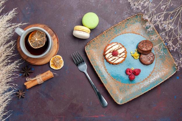 Vista de cima um pequeno bolo cremoso com biscoitos de chocolate e uma xícara de chá em uma superfície escura.