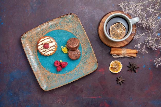 Vista de cima um pequeno bolo cremoso com biscoitos de chocolate e uma xícara de chá na superfície escura bolo de biscoito torta doce biscoito de açúcar