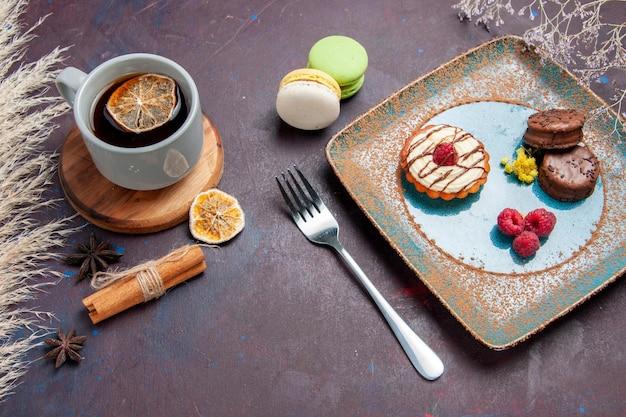 Vista de cima um pequeno bolo cremoso com biscoitos de chocolate e uma xícara de chá na superfície escura de biscoito torta doce bolo de biscoito de açúcar