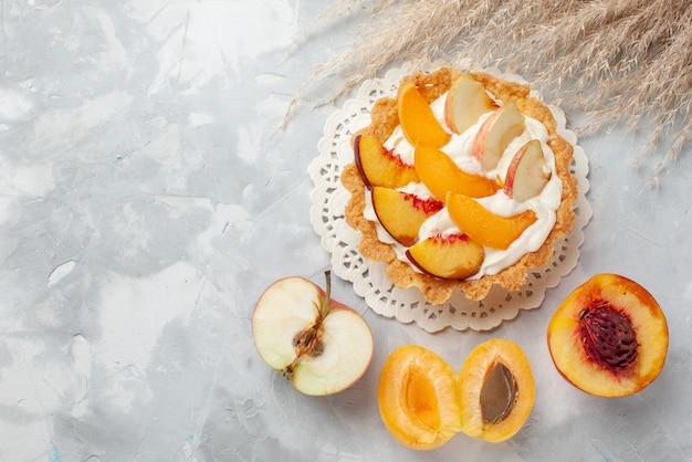 Vista de cima um pequeno bolo cremoso com frutas fatiadas e creme branco, juntamente com damascos frescos e pêssegos em um biscoito de mesa com luz branca