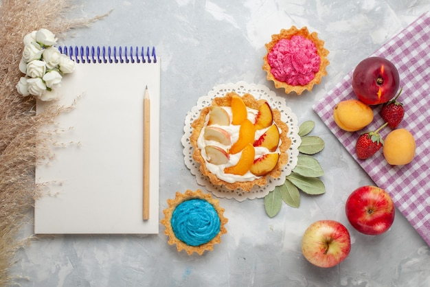 Vista de cima um pequeno bolo cremoso com frutas fatiadas e creme branco junto com bolos cremosos e frutas em um biscoito de bolo de frutas branco claro