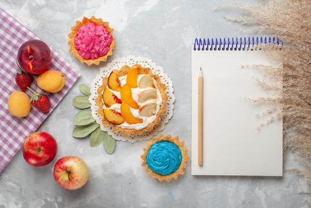 Vista de cima um pequeno bolo cremoso com frutas fatiadas e creme branco junto com bolos cremosos e frutas em um biscoito doce de mesa branco claro