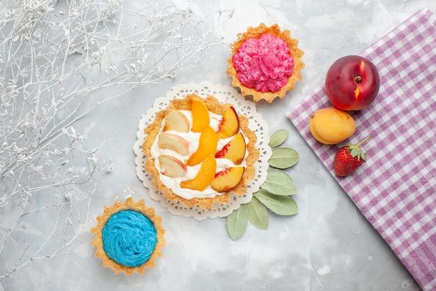 Vista de cima um pequeno bolo cremoso com frutas fatiadas e creme branco junto com bolos cremosos em um biscoito de bolo de frutas leve