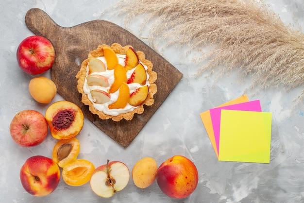Vista de cima um pequeno bolo cremoso com frutas fatiadas e creme branco junto com frutas frescas em um biscoito doce com creme de frutas branco de mesa