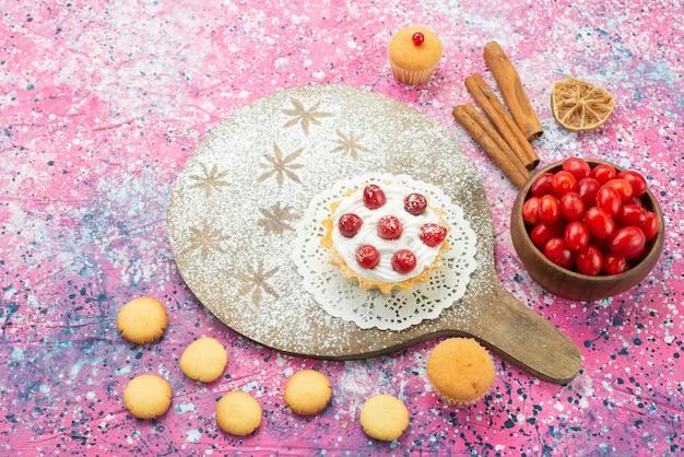 Vista de cima um pequeno bolo cremoso com frutas vermelhas frescas e biscoitos na superfície roxa.