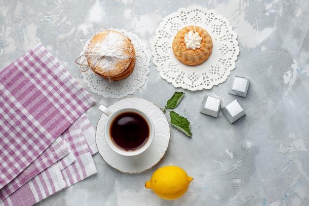 Vista de cima um pequeno bolo delicioso com biscoitos de sanduíche de chá e limão azedo na mesa de luz.