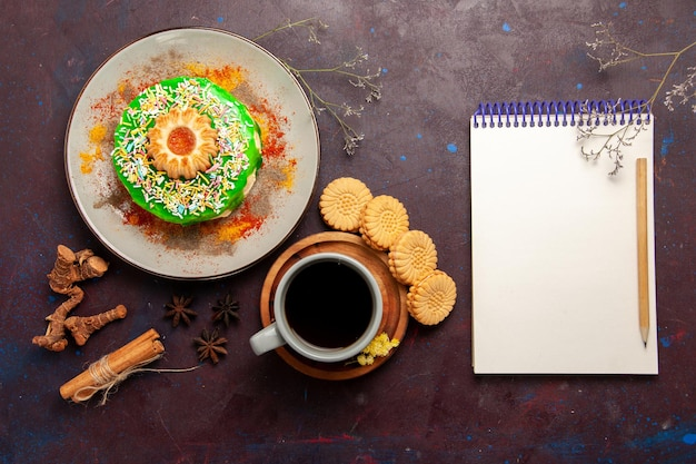 Vista de cima um pequeno bolo delicioso com biscoitos e uma xícara de chá na mesa escura