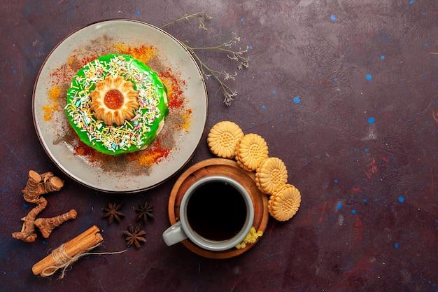 Vista de cima um pequeno bolo delicioso com biscoitos e uma xícara de chá na superfície escura
