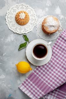 Vista de cima um pequeno bolo delicioso com chá e limão azedo na mesa clara bolo biscoito doce cor de biscoito