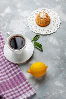 Vista de cima um pequeno bolo delicioso com chá e limão azedo na mesa de luz bolo biscoito biscoito doce