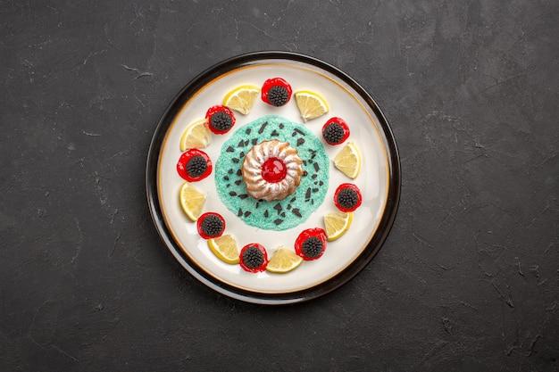 Vista de cima um pequeno bolo delicioso com confitures e rodelas de limão dentro do prato no fundo escuro frutas cítricas biscoito biscoito doce