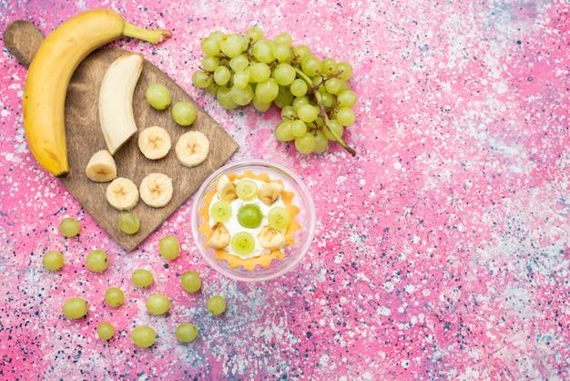 Vista de cima um pequeno bolo delicioso com creme e bananas fatiadas e uvas na superfície brilhante doce de frutas