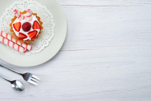 Vista de cima um pequeno bolo delicioso com creme e morangos fatiados dentro do prato no fundo branco bolo de frutas baga