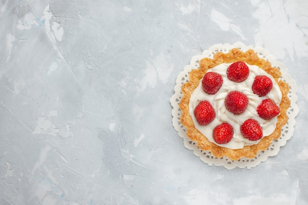 Vista de cima um pequeno bolo delicioso com creme e morangos vermelhos frescos no fundo claro bolo frutas baga biscoito doce creme