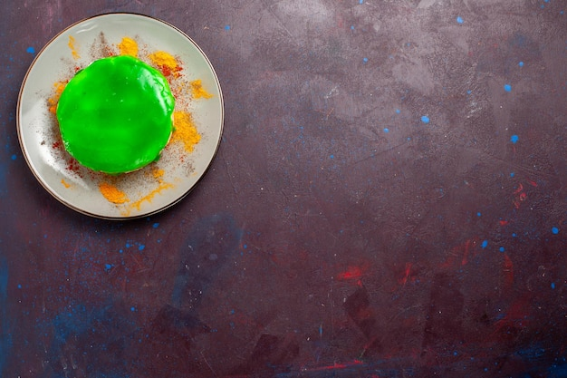 Vista de cima um pequeno bolo delicioso com creme verde dentro do prato na mesa escura