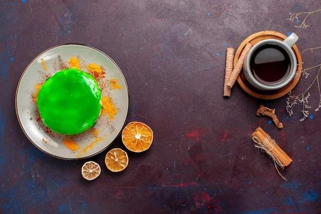 Vista de cima um pequeno bolo delicioso com creme verde e uma xícara de chá na superfície escura