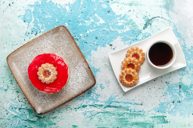 Vista de cima um pequeno bolo delicioso com creme vermelho e biscoitos no fundo azul claro bolo biscoito doce açúcar torta chá