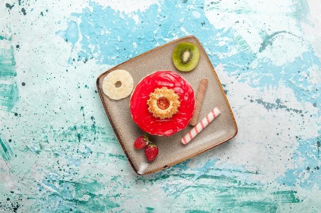 Vista de cima um pequeno bolo delicioso com creme vermelho em um bolo de mesa azul claro biscoito doce com açúcar e chá