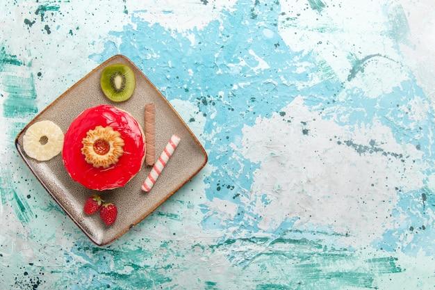Vista de cima um pequeno bolo delicioso com creme vermelho sobre fundo azul claro