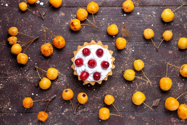 Vista de cima um pequeno bolo delicioso com dogwood junto com cerejas amarelas na mesa de madeira marrom fruta fresca azeda suave Foto gratuita