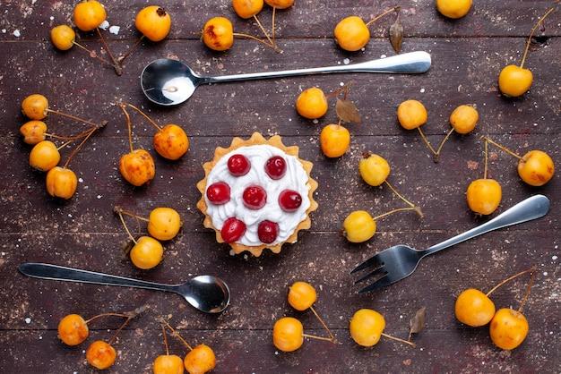Vista de cima um pequeno bolo delicioso com dogwood junto com cerejas amarelas na mesa de madeira marrom frutas frescas azedas maduras maduras