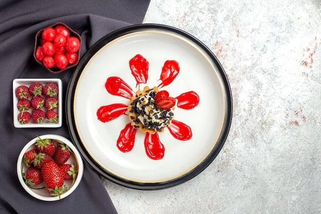 Vista de cima um pequeno bolo delicioso com frutas e doces na superfície branca.