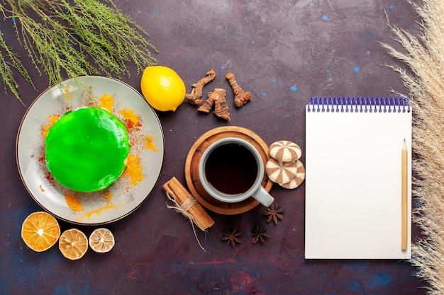 Vista de cima um pequeno bolo delicioso com uma xícara de chá e biscoitos na superfície escura