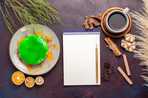 Vista de cima um pequeno bolo delicioso com uma xícara de chá na mesa roxa escura